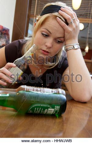 Young blonde alcoholic woman drunk, with empty bottles of
